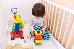 2 años de niño que juega los coches en la cama blanca Foto de archivo libre de regalías