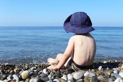 2 años de niño se sientan en la playa de piedra Foto de archivo libre de regalías