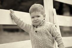 2 años del bebé en una valla de estacas blanca al lado de los hors Imagenes de archivo
