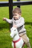 2 años del bebé que juega con el caballo Imagen de archivo