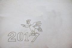 2017 años del gallo, escribiendo en la arena Fotografía de archivo