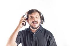 30 años del hombre caucásico gozan para escuchar música de los auriculares Imagenes de archivo