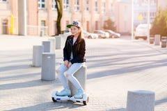 10 años del montar a caballo de la muchacha en el uno mismo que equilibra el monopatín eléctrico Fotos de archivo libres de regalías