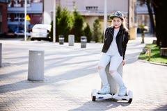 10 años del montar a caballo de la muchacha en el uno mismo que equilibra el monopatín eléctrico Fotos de archivo