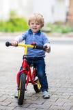 2 años del montar a caballo del niño en su primera bici Fotografía de archivo