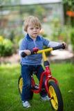 2 años del montar a caballo del niño en su primera bici Imagen de archivo libre de regalías