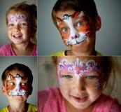 6 años del muchacho con los ojos azules hacen frente a la pintura de un gato o de un tigre Muchacha de ojos azules bastante emoci Fotografía de archivo