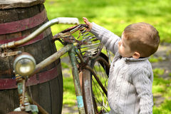 2 años del muchacho curioso que camina alrededor de la bici vieja Foto de archivo