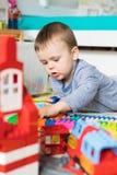 3 años del muchacho de la estructura de la casa del lego Fotos de archivo