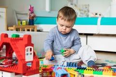 3 años del muchacho de la estructura de la casa del lego Imagen de archivo