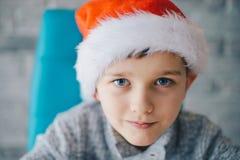 8 años del muchacho en el casquillo de Santa Claus Fotos de archivo libres de regalías