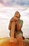 13 años del muchacho en una bala de heno en campo Fotos de archivo libres de regalías