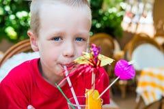 5 años del muchacho que bebe un cóctel Imágenes de archivo libres de regalías