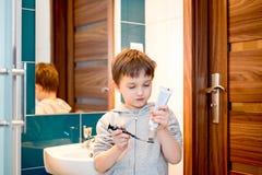 7 años del muchacho que cepilla sus dientes en el cuarto de baño Fotos de archivo