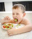 4 años del muchacho que come la ensalada Foto de archivo libre de regalías