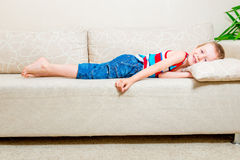6 años del muchacho que miente en el sofá Imagen de archivo libre de regalías