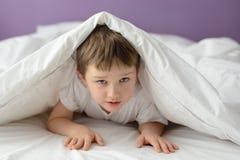 7 años del muchacho que oculta en cama debajo de una manta o de una sobrecama blanca Imágenes de archivo libres de regalías