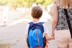 7 años del muchacho que va a la escuela con su madre imagen de archivo