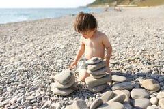 2 años del niño de guijarros del edificio se elevan en la playa Imagen de archivo