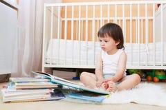 2 años del niño de libros de lectura contra la cama blanca Imagenes de archivo