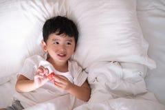 3 años del pequeño muchacho asiático lindo en casa en la cama, mentira del niño Foto de archivo