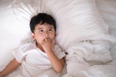 3 años del pequeño muchacho asiático lindo en casa en la cama, mentira del niño Imagenes de archivo