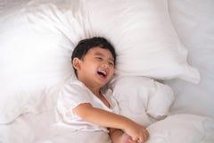 3 años del pequeño muchacho asiático lindo en casa en la cama, mentira del niño Fotografía de archivo