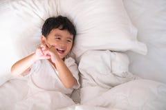 3 años del pequeño muchacho asiático lindo en casa en la cama, mentira del niño Imagen de archivo libre de regalías