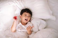 3 años del pequeño muchacho asiático lindo en casa en la cama, mentira del niño Imagen de archivo