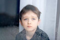 7 años deprimidos de niño del muchacho que mira hacia fuera la ventana Foto de archivo libre de regalías
