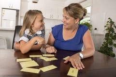 6 años dulces y felices preciosos de la hija que aprende la lectura con la cocina del juego de palabras de la tarjeta flash en ca Fotos de archivo libres de regalías