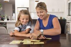 6 años dulces y felices preciosos de la hija que aprende la lectura con la cocina del juego de palabras de la tarjeta flash en ca Imagen de archivo