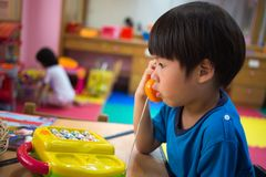4 años el jugar asiático del muchacho cogen el teléfono del juguete Fotos de archivo