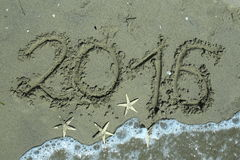 2016 años en la arena y tres estrellas de mar Fotos de archivo libres de regalías