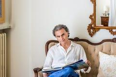 Años 40 encantadores que leen el libro de la foto en sala de estar Fotos de archivo
