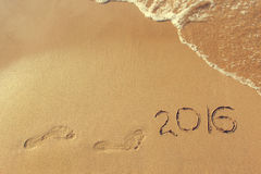 2016 años escritos y huella en el mar de la playa arenosa Imagen de archivo