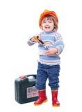 Bebé feliz en el casco de protección con las herramientas Imagen de archivo