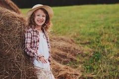 7 años felices de la muchacha del niño en la camisa y el sombrero de tela escocesa del estilo rural que se relajan en campo del v Fotos de archivo