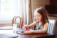 8 años felices de la muchacha del niño que desayuna en cocina del país Fotos de archivo libres de regalías