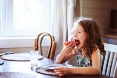 8 años felices de la muchacha del niño que desayuna en cocina del país Imagen de archivo