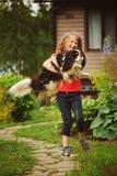 8 años felices de la muchacha del niño que juega con su perro del perro de aguas al aire libre Imagen de archivo libre de regalías