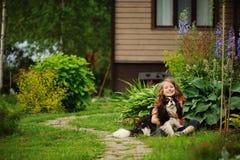 8 años felices de la muchacha del niño que juega con su perro del perro de aguas al aire libre Foto de archivo libre de regalías