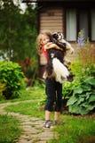 8 años felices de la muchacha del niño que juega con su perro del perro de aguas al aire libre Imágenes de archivo libres de regalías