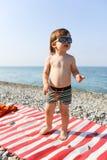 2 años felices de muchacho en gafas de sol en la playa de piedra Imagenes de archivo