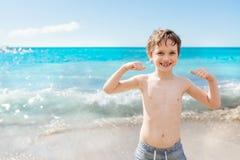 7 años felices de muchacho en gesto del éxito de la victoria en la playa Foto de archivo