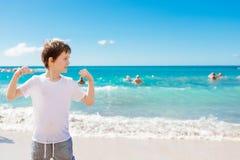 7 años felices de muchacho en gesto del éxito de la victoria en la playa Fotos de archivo libres de regalías