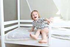2 años felices de niña en su cama Imagen de archivo