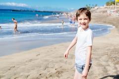 7 años felices de niño del muchacho que camina en la playa Imagen de archivo libre de regalías