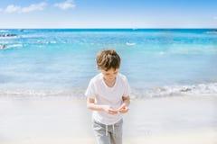 7 años felices de niño del muchacho que camina en la playa Imagenes de archivo