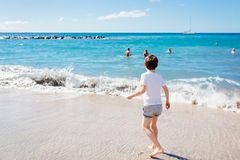 7 años felices de niño del muchacho que camina en la playa Fotos de archivo